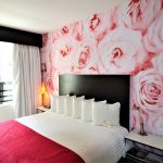 Room with a king size bed and a red roses wallpaper in the back
