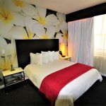 Room with a standard size bed and a white flower wallpaper in the back