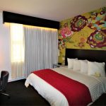 Room with a standard size bed and a flower wallpaper in the back