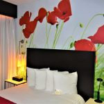Room with a standard size bed and a red flower wallpaper in the back