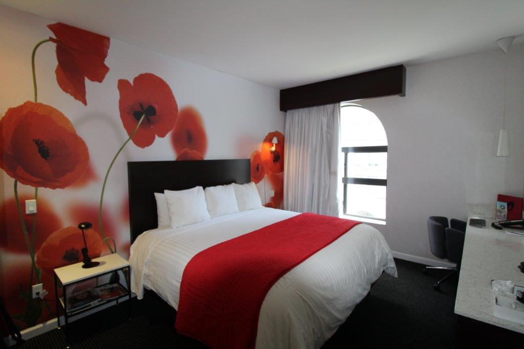 Room with a standard size bed and a red flower wallpaper in the back - links to flower suite